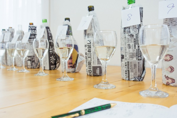 saketaku日本酒完全ブラインドテストで新聞紙で包んだ日本酒のボトルの画像